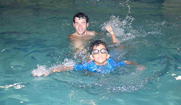 male swim instructor with child in pool for swim lessons