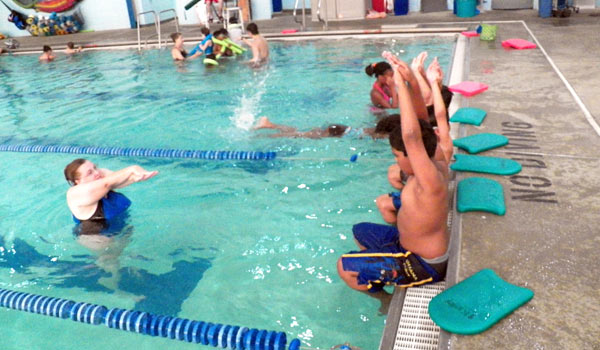 instructor with group of children for swim lesson