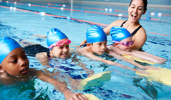 children group swim lesson with female instructor